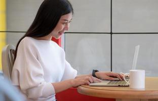 Young college student using a laptop to chat online with a happy smile. photo