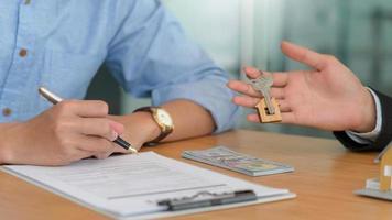 firma de contrato y entrega de llaves de casa para compraventa de viviendas. foto