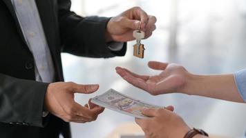 Toma recortada de intercambio de dólares y llaves de casa entre comprador y vendedor. foto