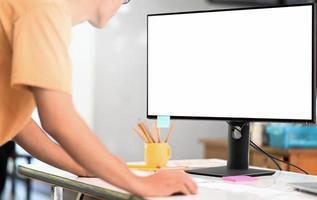 joven operando una computadora de maqueta con una gran pantalla en blanco, usando una computadora para buscar información. foto