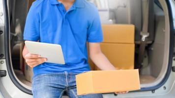 El repartidor sentado en el coche usa una tableta y sostiene una caja de paquetes para entregar la mercancía al cliente. foto