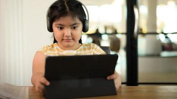 The girl is wearing headphones intently looking at the tablet. photo