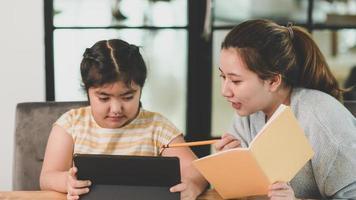 Tutor teaching child girls homework. photo