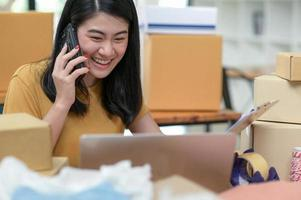A woman uses her phone to confirm online orders. photo