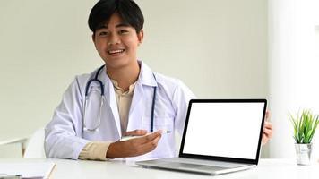 El médico especialista con una bata de laboratorio y un estetoscopio está usando una computadora portátil para guiar a los pacientes, el médico está usando una computadora portátil para recomendar tratamientos en línea. foto