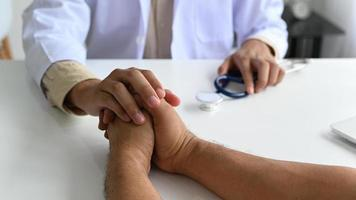 A medical professional in a lab gown with a stethoscope holds the patient hand to comfort, The doctor grabs the patient's hand to encourage. photo