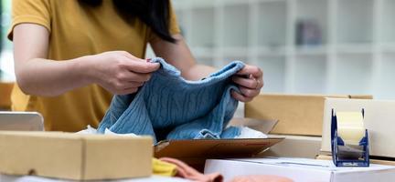 los vendedores en línea están revisando los suéteres de punto antes de empacarlos para el envío. foto