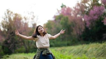 Asian girl smiles mischievously and turns towards the camera during a nature tour. photo