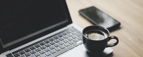 taza de café colocada en la computadora portátil con gráfico de acciones en la pantalla, primer plano. foto