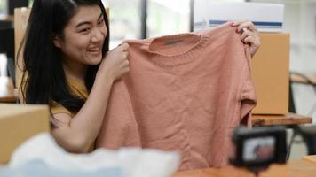 una mujer sosteniendo una camiseta tomando una selfie para vivir la venta en línea, la venta en línea. foto