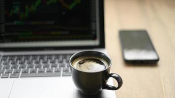taza de café colocada en la computadora portátil con un gráfico de valores en la pantalla, tomada desde el frente. foto
