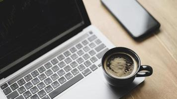 taza de café colocada en la computadora portátil con gráfico de acciones en la pantalla, vista superior. foto