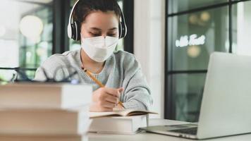 chica asiática con estetoscopio con máscara médica tomando notas y estudiando en línea con una computadora portátil. foto