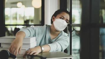 A Female asian student wearing a medical mask sits by the window looking out. photo