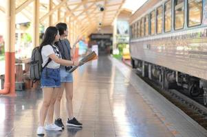 Two teenage girls looking at maps to travel by train. photo
