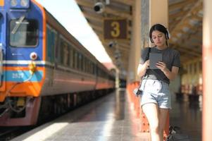 A teenage woman wearing headphones listening to music from an app on her tablet while waiting for a train.. photo