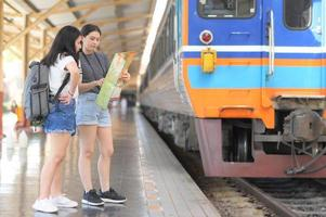 Two teenage girls looking at a map to travel by train. photo