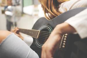 detalles de guitarra acústica en la mano de una mujer zurda foto