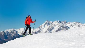 una mujer solitaria camina sobre la nieve con crampones foto