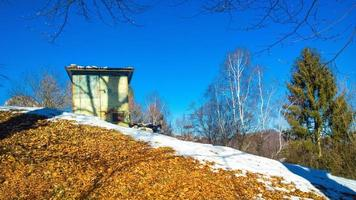 camouflaged wooden hut for hunting in the mountains in winter photo