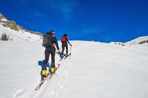 Ski mountaineering two girl uphill towards a mountain photo