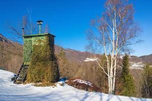 Cabaña de madera camuflada para cazar en las montañas en invierno foto
