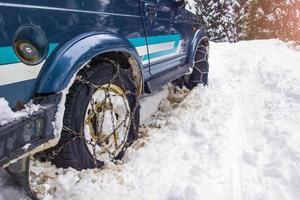Autos fuera de la carretera con cadenas en dificultad en la nieve. foto