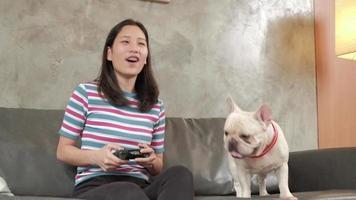 une jeune femme asiatique décontractée joue à une console de jeux vidéo avec plaisir et excitation contrôlés par un joystick sur un canapé dans le salon de la maison. l'animal de compagnie est un chien, bouledogue français regardant de près. video