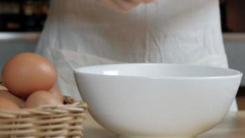 Close-up front view footage, a female cook in a white apron is cracking an egg into a cup to prepare a meal on a wooden table in the home's kitchen. Eating egg yolks is a healthy breakfast. video