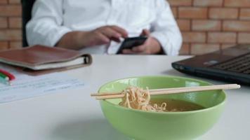 trabajador masculino ocupado trabajando con una computadora portátil y un teléfono móvil, use palillos para comer fideos instantáneos durante la hora del almuerzo en la oficina, porque es rápido, sabroso y barato. con el tiempo comida rápida asiática, estilo de vida poco saludable. video