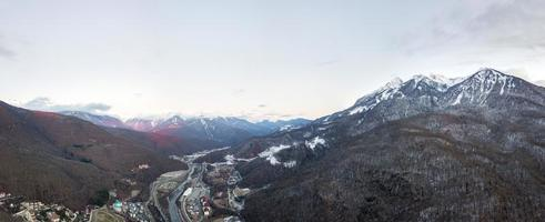 Aerial view of Krasnaya Polyana on sunset, mountains covered by snow. Russia. photo