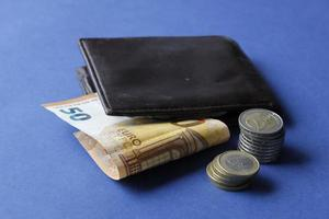 Fifty euro banknote, stacked coins and brown leather wallet on the blue background photo