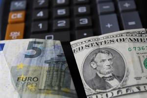 Approach to euro banknote of five euro and american five dollars bill on the calculator photo