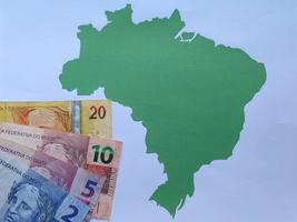 Brazilian banknotes and background with Brazil map silhouette photo