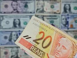 Approach to brazilian banknote of twenty reais and background with american dollar bills photo