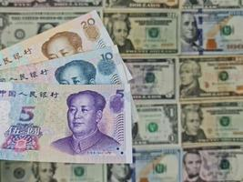 Approach to chinese banknotes and background with american dollar bills photo