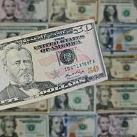 Approach to american fifty dollars banknote and background with american dollar bills photo