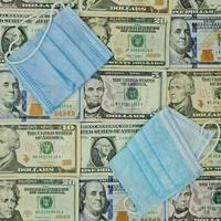 Disposable face masks and background with american dollar bills, view from above photo