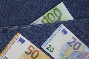 European banknotes of different denomination between blue denim fabric photo