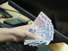 Hand of a woman holding Brazilian money on a computer keyboard photo