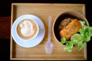 Coffee cup with latte art in a swan shape and Fried salmon steak photo