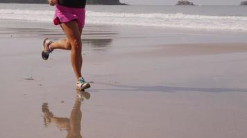 tiro de cámara lenta de primer plano de mujer corriendo en la playa. filmado en rojo épico para una resolución de alta calidad de 4k, uhd, ultra hd. video