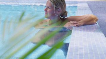 donna che si rilassa in piscina. girato in rosso epico per una risoluzione 4k, uhd, ultra hd di alta qualità. video