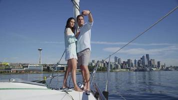 ungt par på segelbåt tillsammans med mobiltelefon. sköt på röd epik för högkvalitativ 4k, uhd, ultrahd -upplösning. video