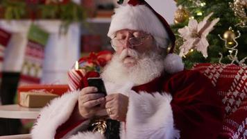 jultomten sms: ar med mobiltelefon och tar selfie video