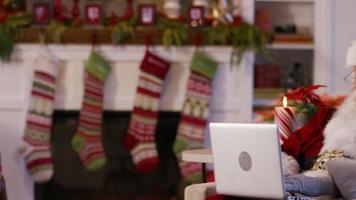de kerstman met behulp van laptop in de woonkamer video