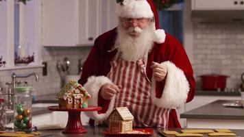 Papá Noel en la cocina decorando la casa de pan de jengibre video