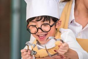 Cute little Asian happy boy interested in cooking with mother funny in home kitchen. People lifestyles and Family. Homemade food and ingredients concept. Two people baking Christmas cake and cookies photo