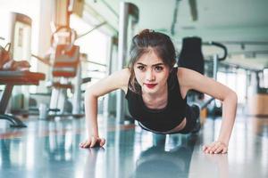 chica de fitness mujer asiática hacer empujones en el gimnasio. concepto de salud y salud. tema de entrenamiento y desarrollo corporal. concepto de fuerza y belleza foto