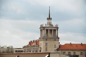 Edificio pico sobre los tejados rojos de la ciudad en el cielo nublado foto